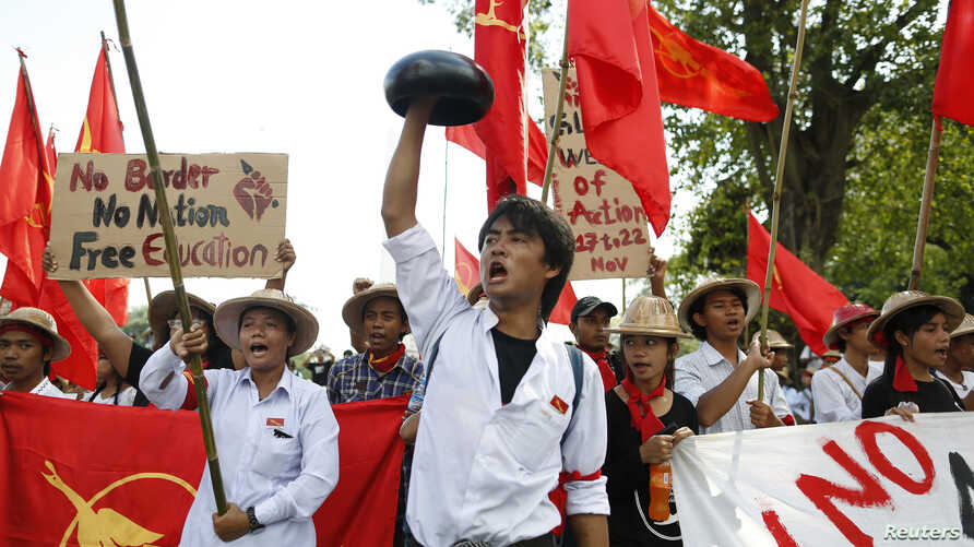 A student carries a monk's alms bowl turned upside down over his head, a Burmese symbol of protest, during a rally against education law in central Yangon, Nov. 17, 2014.