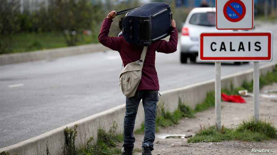 FILE - A migrant carries his belongings as he departs a camp in Calais, France, Oct. 22, 2016.