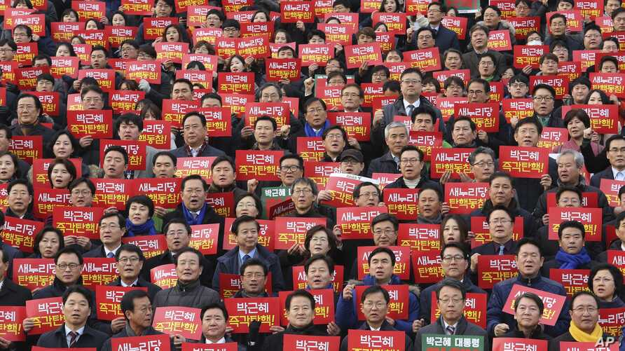 Lawmakers and members of opposition parties hold cards during a rally demanding the impeachment of South Korean President Park Geun-hye at the National Assembly in Seoul, South Korea, Dec. 7, 2016.