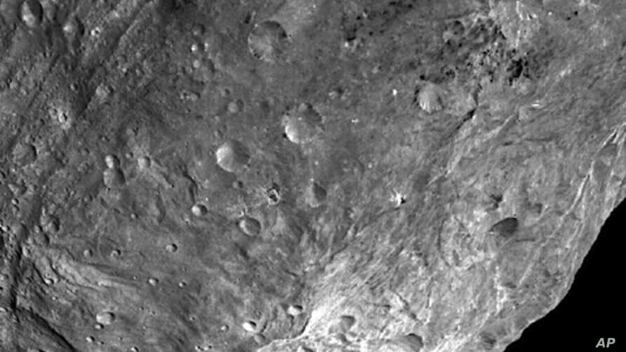 In this image, obtained by Dawn's framing camera, a peak at Vesta's south pole is seen at the lower right. The grooves in the equatorial region are about 10 kilometers wide. The image was taken on July 24, 2011, from a distance of about  5,200 kilome