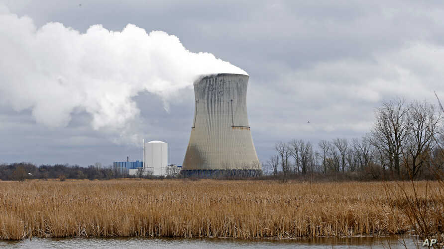 FILE – Steam rises from the cooling tower of FirstEnergy C