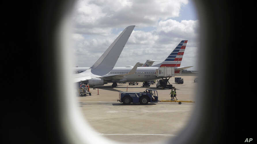FILE- American Airlines aircraft sit at O'Hare International Airport in Chicago, June 16, 2018. Newer seat-back entertainment systems on some airplanes operated by American Airlines and Singapore Airlines have cameras, and it's likely they are also o