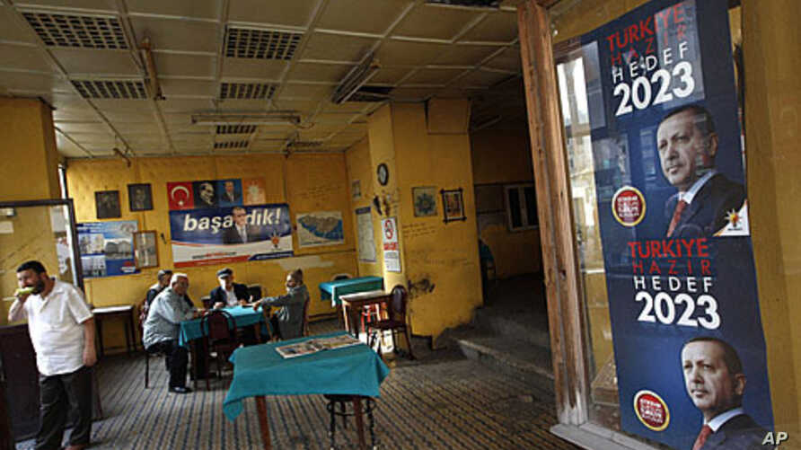 Men sit in a tea house in Istanbul, with a campaign poster of Prime Minister Recep Tayyip Erdogan on display nearby, June 9, 2011