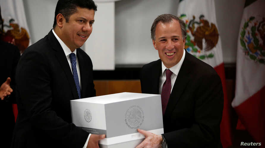 Mexico's Finance Minister Jose Antonio Meade (R) hands over the 2017 budget to the Chamber of Deputies chairman Javier Bolanos in Mexico City, Mexico, Sept. 8, 2016.