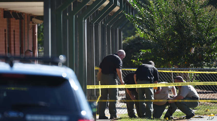Members of law enforcement investigate an area at Townville Elementary School in Townville, S.C., after a shooting, Sept. 28, 2016.