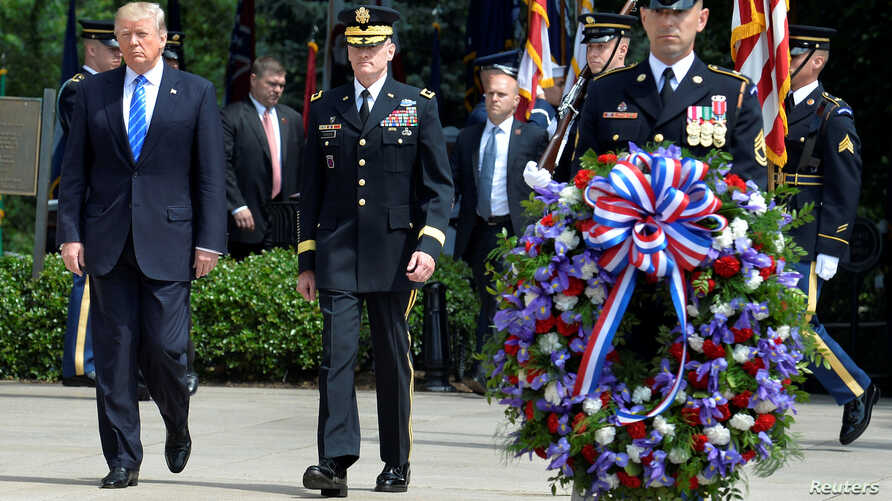 US President Donald Trump (L) is escorted for a ceremony to lay a wreath at the Tomb of the Unknown Soldier at Arlington National Cemetery, as part of Memorial Day observance, Arlington, Virginia, May 29, 2017.