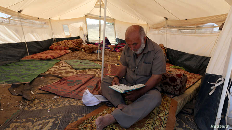 A Palestinian man reads the Koran inside a tent during the holy month of Ramadan, at a protest camp near the Israel-Gaza border in the central Gaza Strip, May 17, 2018.