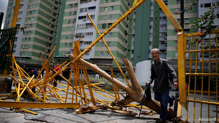 A man walks through a broken main gate after opposition supporters and security forces clashed in and outside residential buildings on Tuesday according to residents, in Caracas, Venezuela, June 14, 2017.
