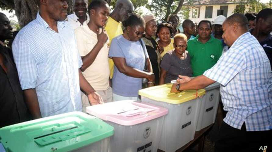 The returning officer for Mvita Constituency, Mombasa,  Gabriel Mwalenga, right, explains to registered voters how the ballot boxes will be used in the forthcoming general elections during an election mock voting exercise organized by the IEBC and sp
