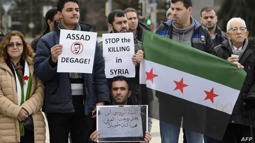 """Demonstrators holding a Free Syria flag and placards reading """"Stop the killing in Syria"""" take part in a protest outside the United Nations (UN) offices in Geneva, on Jan. 29, 2016 on the opening day of Syrian peace talks."""