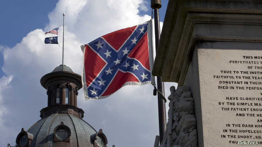 FILE - The U.S. flag and South Carolina state flag flies at half staff to honor the nine people killed in the Charleston murders as the confederate battle flag also flies on the grounds of the South Carolina State House in Columbia, S.C., June 20, 20