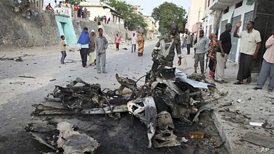 Somalis observe the remains of a vehicle used in a car bomb attack in the capital Mogadishu, Somalia, February 8, 2012.