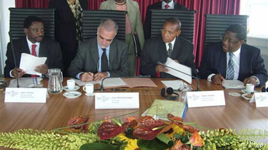 In this photo taken by International Criminal Court, first row from left: Kenya's Justice Minister Mutula Kilonzo, ICC's prosecutor Luis Moreno-Ocampo, Kenya's Minister of Lands James Orengo, as they sign an agreement at ICC in The Hague, Netherlands