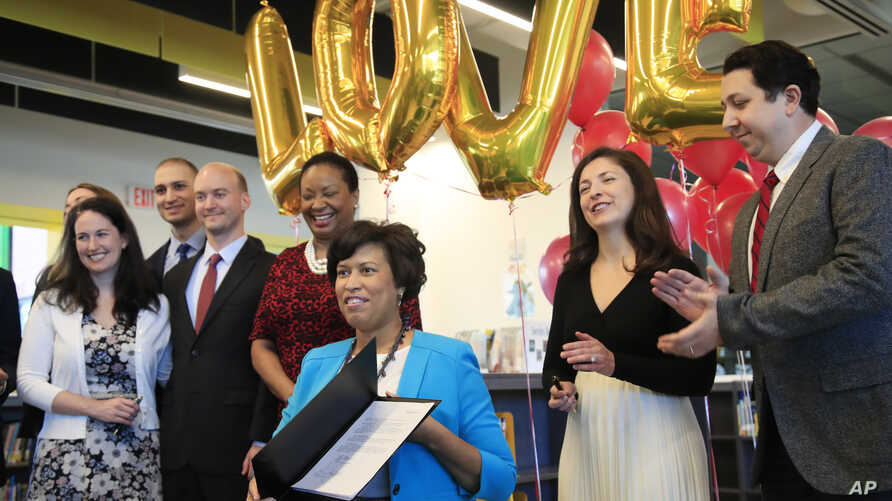 District of Columbia Mayor Muriel Bowser, seated, holds the LOVE Act she signed, Jan. 11, 2019.