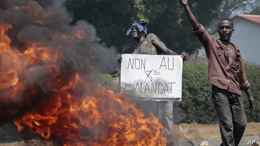 "An opposition demonstrator holds a sign in French reading ""No to a third term"" next to a barricade fire set by protesters in the Ngagara neighborhood of Bujumbura, Burundi, June 3, 2015."