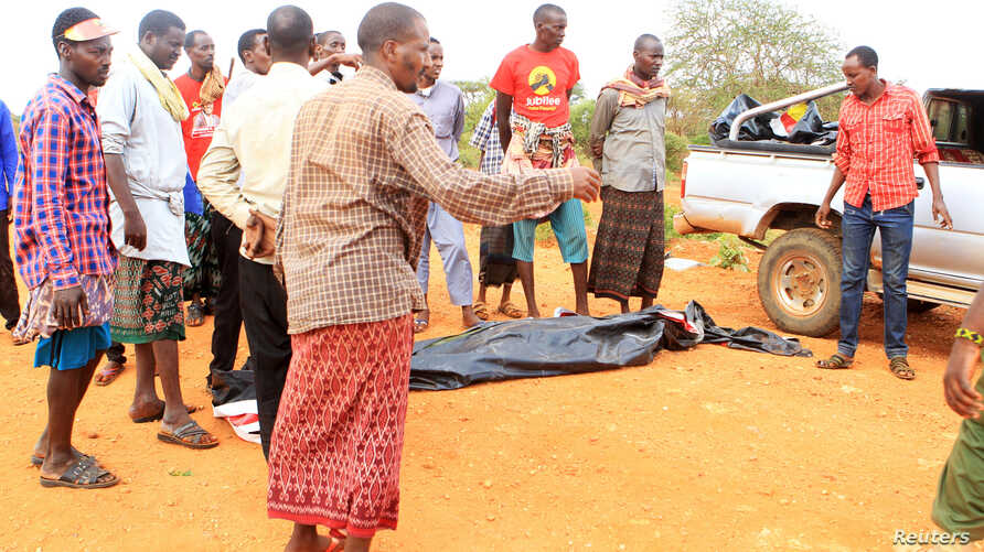 People stand near a body at the scene where a blast killed Kenyan police officers at the Garissa county, eastern Kenya, May 24, 2017.