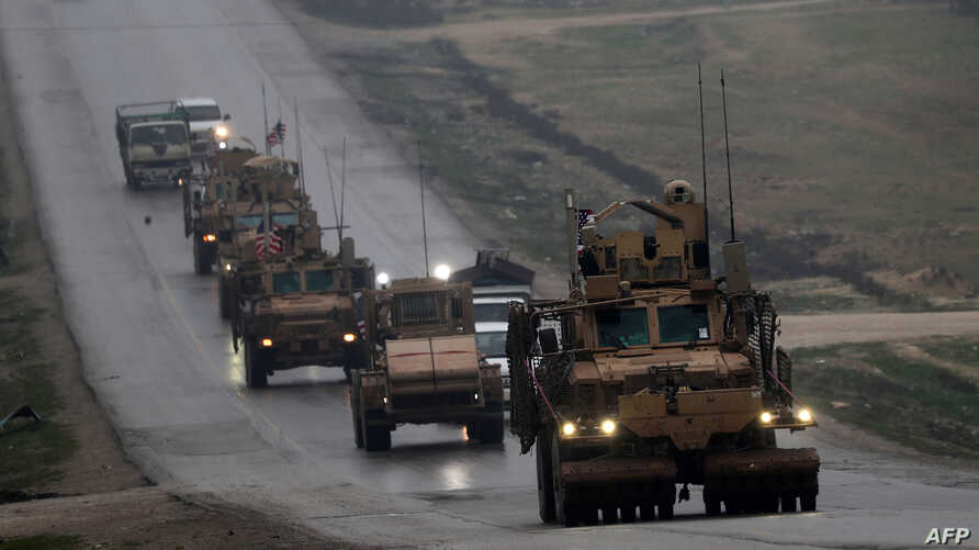 FILE - A convoy of US military vehicles is seen in Syria's northern city of Manbij, Dec. 30, 2018.