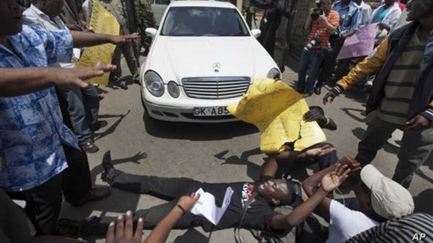 Protester lays down outside Kenyan Parliament to block legislators from leaving, Nairobi, Oct. 9, 2012.