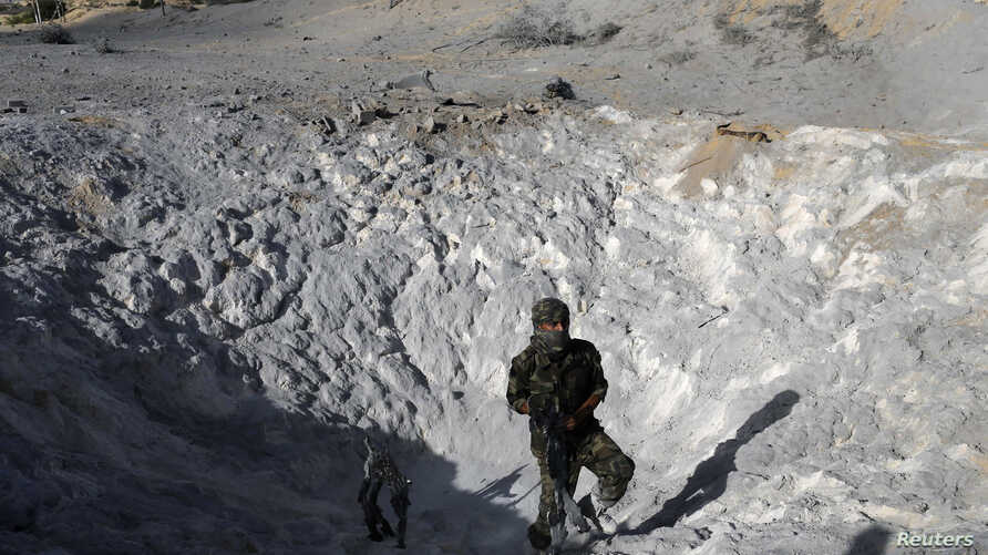 A Palestinian militant inspects a crater caused by what police said was an Israeli air strike in Khan Younis in the southern Gaza Strip, June 29, 2014.