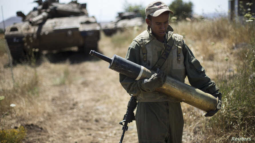 An Israeli soldier carries a tank shell near Alonei Habashan on the Israeli occupied Golan Heights, close to the ceasefire line between Israel and Syria June 22, 2014.