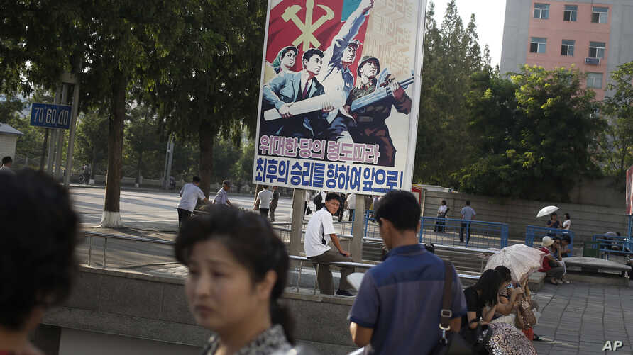 A man sits under a propaganda banner in Pyongyang, North Korea, Aug. 23, 2015.