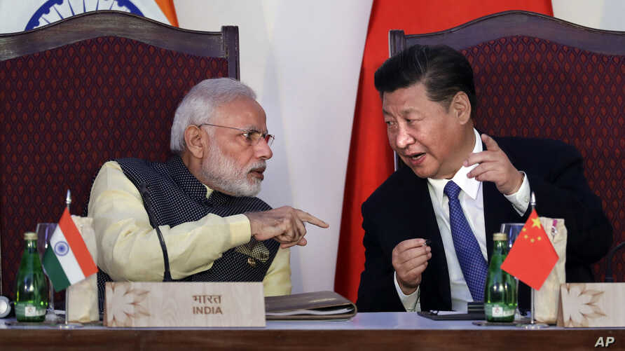 FILE - Indian Prime Minister Narendra Modi, left, talks with Chinese President Xi Jinping during the BRICS summit in Goa, India, Oct. 16, 2016. China and India may have ended a tense border standoff for now, but their longstanding rivalry raises ques...