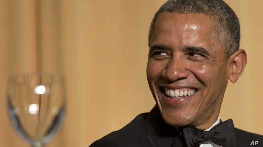 President Barack Obama laughs as actor and comedian Joel McHale speaks during the White House Correspondents' Association Dinner at the Washington Hilton Hotel, May 3, 2014, in Washington.