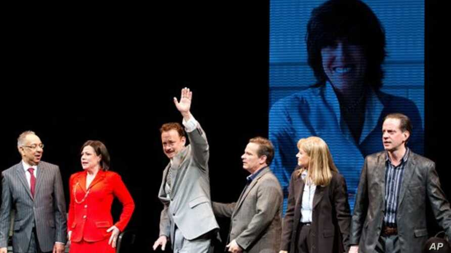 """George C. Wolfe , Maura Tierney, and Tom Hanks, with an image of Nora Ephron behind them on a large screen, at the """"Lucky Guy"""" opening night, April, 1, 2013 in New York, NY."""