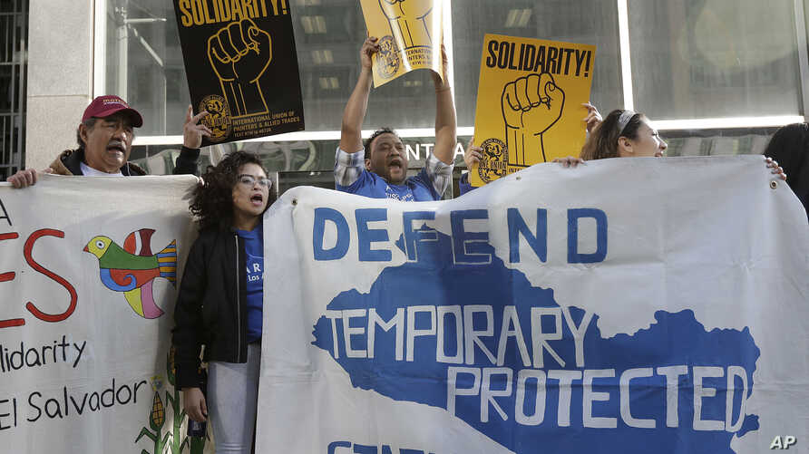 FILE Supporters of temporary protected status immigrants hold signs and cheer at a rally before a news conference announcing a lawsuit against the Trump administration over its decision to end a program that lets immigrants live and work legally in t