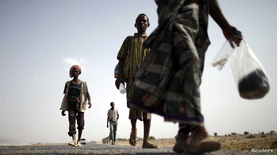 FILE - Ethiopian migrants walk on the side of a highway leading to the western Yemeni town of Haradh, on the border with Saudi Arabia, March 28, 2012.