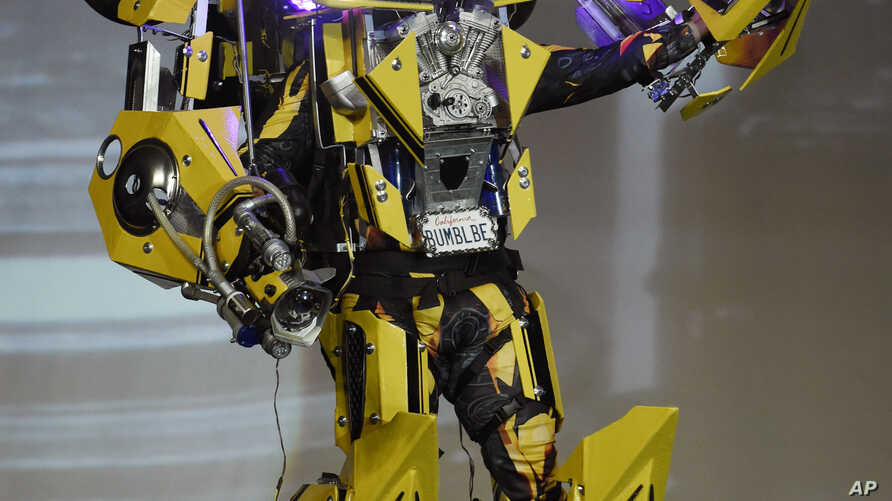 """Contestant """"Bumblebee"""" waves to the crowd during the 41st Annual Comic-Con Masquerade costume competition in San Diego, California, July 11, 2015."""