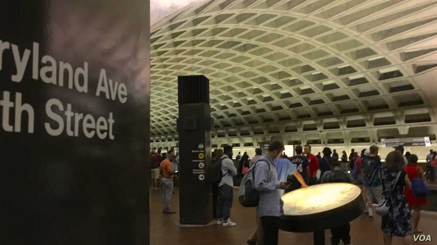 A tourist consults a map of the DC metro system while waiting for a train at the L'Enfant Plaza metro stop on August 9. 2016. (VOA/Maddux)