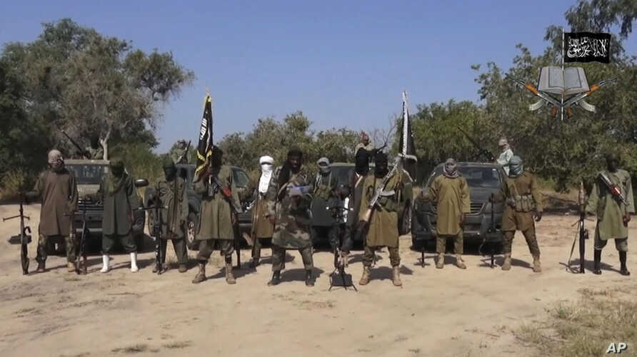FILE - In this file image taken from video released, Oct. 31, 2014, by Boko Haram, shows Abubakar Shekau, centre, the leader of Nigeria's Islamic extremist group.