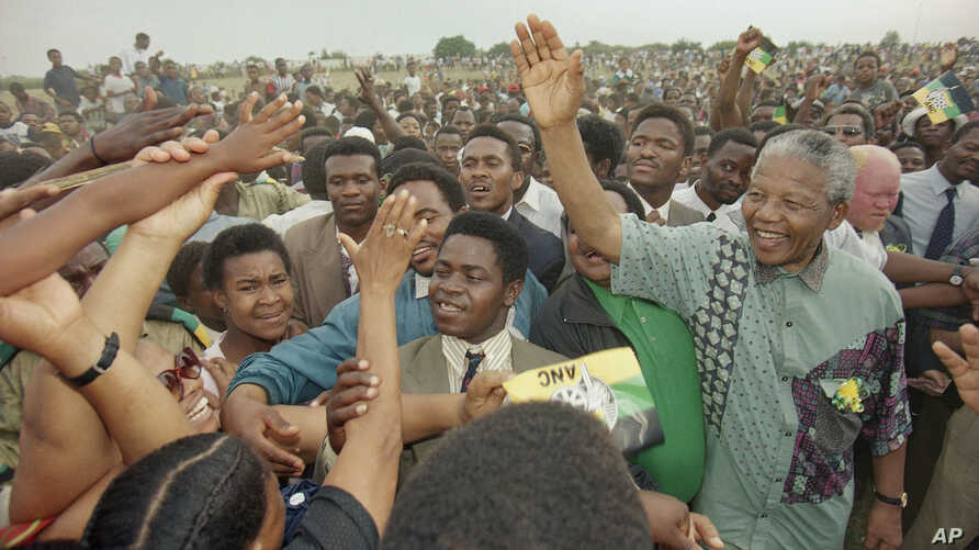 African National Congress President Nelson Mandela, right, waves to the gathered crowd at Jouberton Township stadium as people reach out to touch him during a campaign rally, Sunday, Jan. 30, 1994.