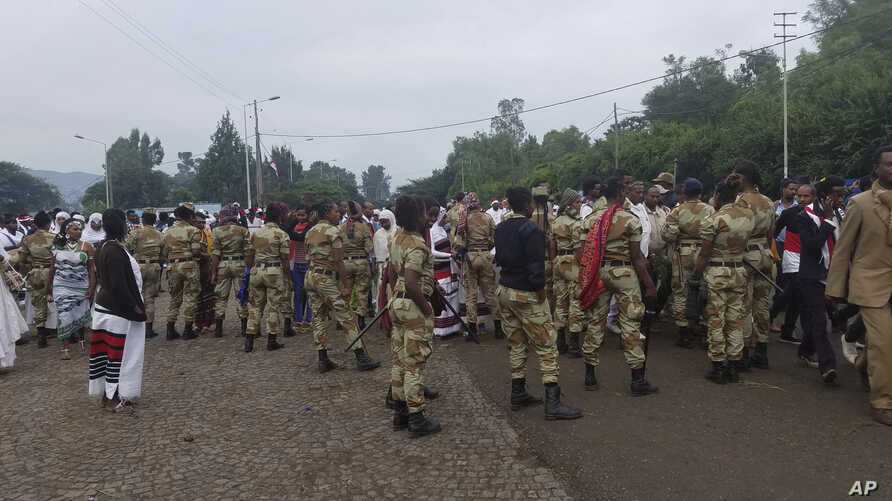 Ethiopian soldiers block the street as people march during an annual religious festival in Bishoftu, a town southeast of Ethiopia's capital, Addis Ababa, Sunday, Oct. 2, 2016.