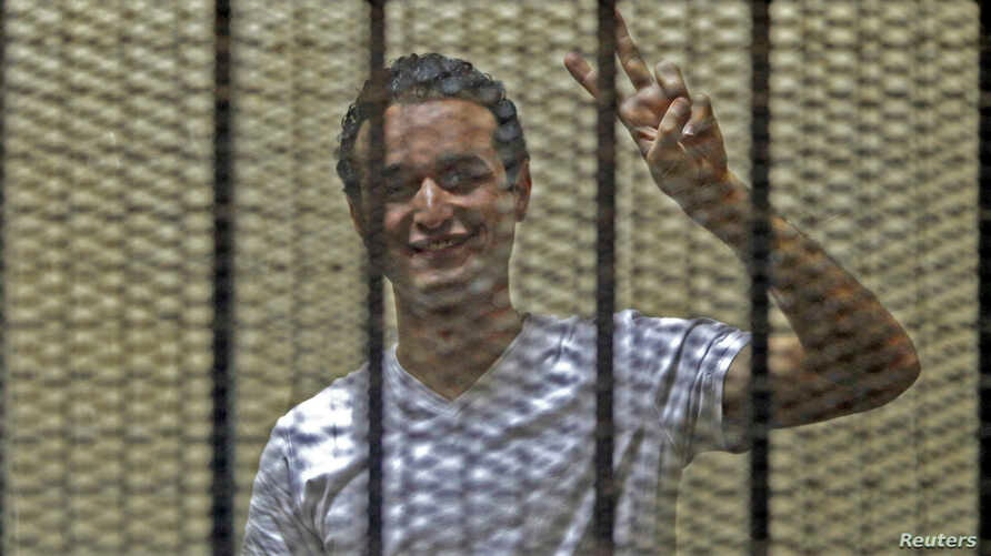 FILE - Egyptian activist Ahmed Douma gestures from behind bars at the New Cairo court, on the outskirts of Cairo.