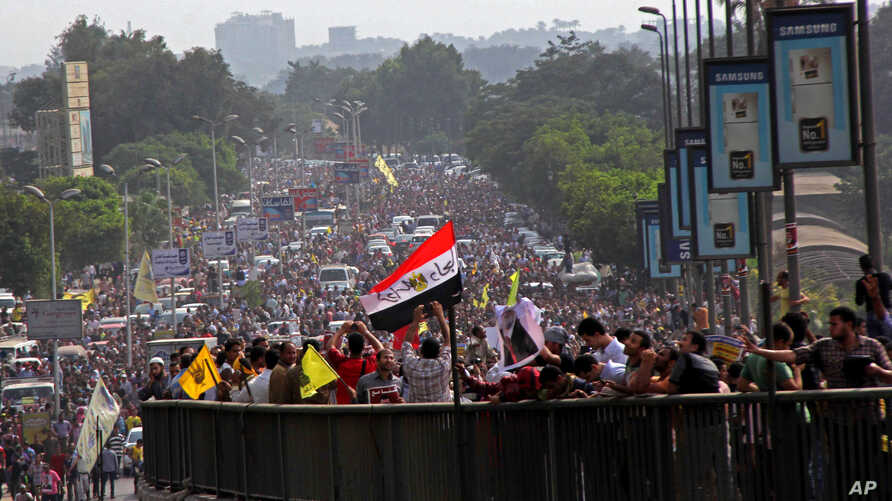 Supporters of Egypt's ousted President Mohamed Morsi stand on a bridge as they march during his trial in Cairo, Egypt, Nov. 4 2013.