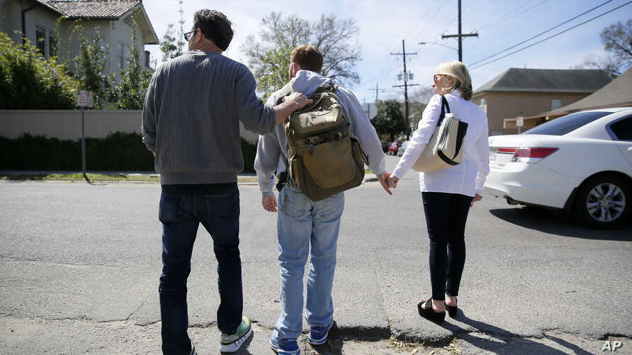FILE - Parents help their son, Ben, cross a street in New Orleans, Louisiana, March 2, 2016. Ben was diagnosed with autism when he was two and a half years old.