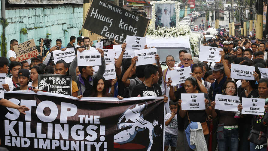 Protesters and supporters carry banners and placards as they march with the hearse of slain Kian Loyd delos Santos, a 17-year-old student, during his funeral, Aug. 26, 2017, in suburban Caloocan city north of Manila, Philippines. The killing of Kian ...