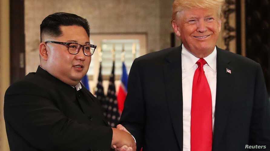U.S. President Donald Trump and North Korea's leader Kim Jong Un shake hands after signing documents during a summit at the Capella Hotel on the resort island of Sentosa, Singapore, June 12, 2018.