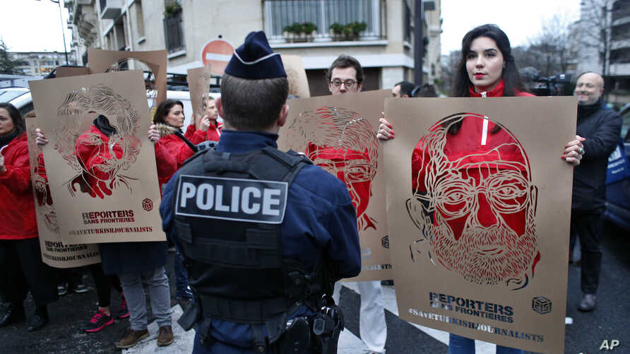 Members of Reporters Without Borders hold stencils representing portraits of detained Turkish journalists, during a demonstration in front of the Turkish embassy, in Paris, Jan. 5, 2018.