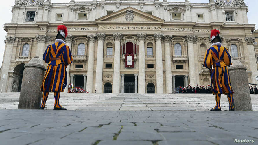 """Two Swiss Guards stand as Pope Francis waves as he delivers his first """"Urbi et Orbi"""" (to the city and world) message from the balcony overlooking St. Peter's Square at the Vatican, Dec. 25, 2013."""