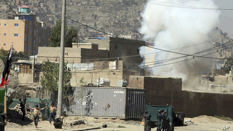 Smoke rises from a house where suspected attackers were hiding while policemen arrests two suspects, left, in Kabul, Afghanistan, Aug. 21, 2018.