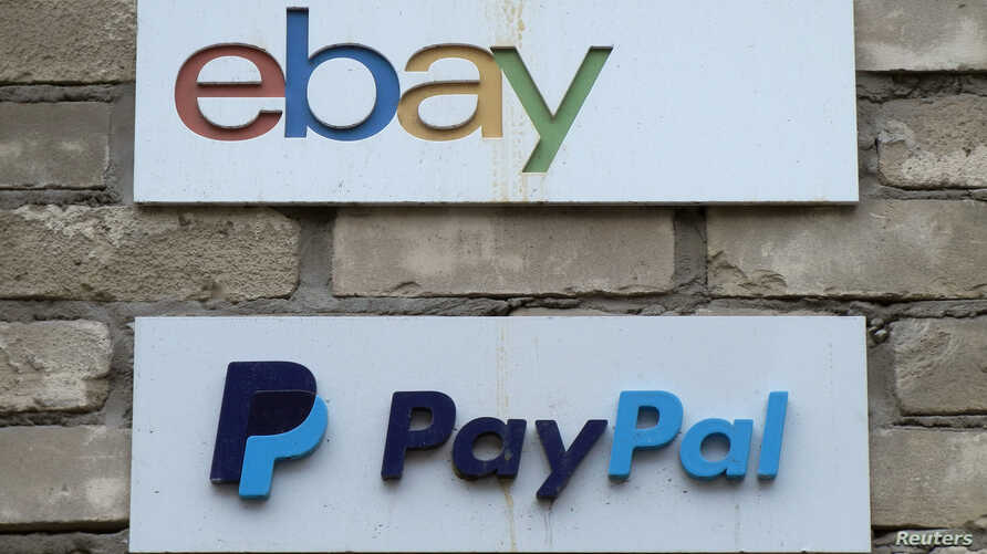 FILE - Signs are posted outside the offices of online marketplace eBay and its electronic payments division PayPal in Toronto, Canada.