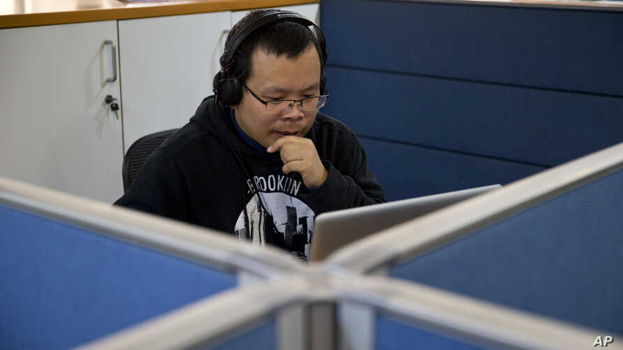 FILE - Chinese journalist Li Xin talks to an Associated Press reporter over Skype, at the Associated Press office in New Delhi, India, Nov. 20, 2015.