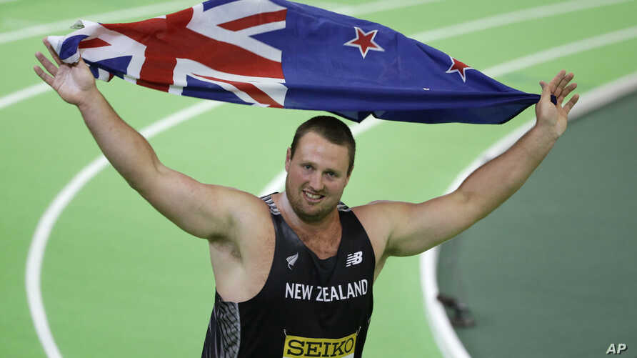 FILE - New Zealand's Tomas Walsh celebrates with a flag after he won the the men's shot put final during the World Indoor Athletics Championships, March 18, 2016, in Portland, Ore.