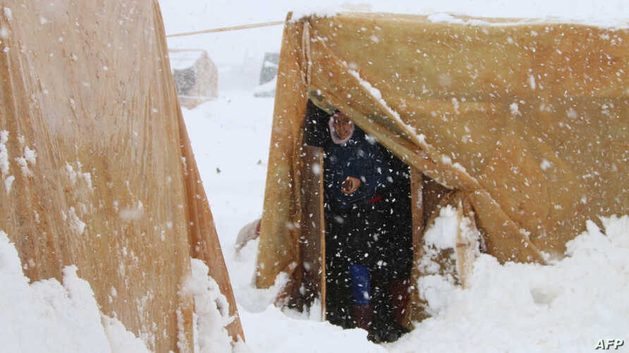 A Syrian refugee stands at the entrance of her tent during a snow storm at an unofficial camp on the road between Riyaq and Baalbek in Lebanon's eastern Bekaa Valley, near the border with Syria, Jan. 7, 2015.