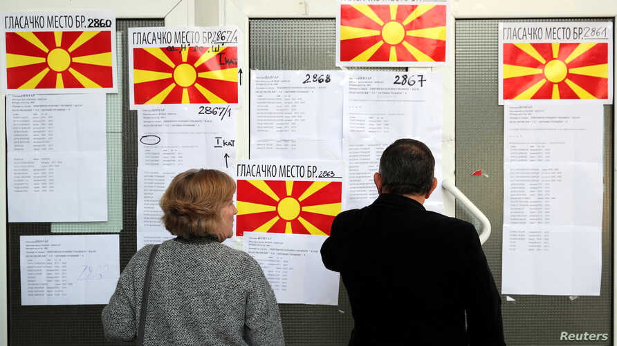 People look for their name on a list as they come to cast their ballot for the referendum in Macedonia on changing the country's name that would open the way for it to join NATO and the European Union in Skopje, Macedonia, Sept. 30, 2018.