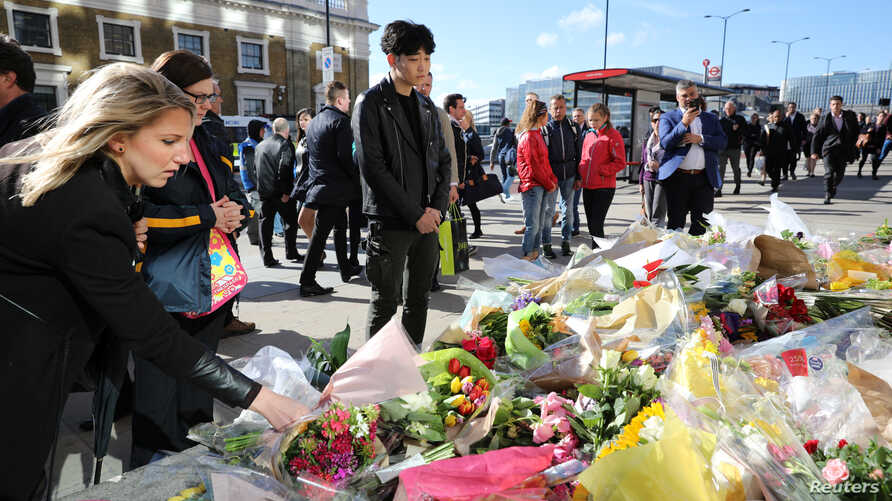 Pedestrians walk over London Bridge, and look at floral tributes, near the scene of the recent attack on London Bridge and Borough Market, London, Britain June 6, 2017.