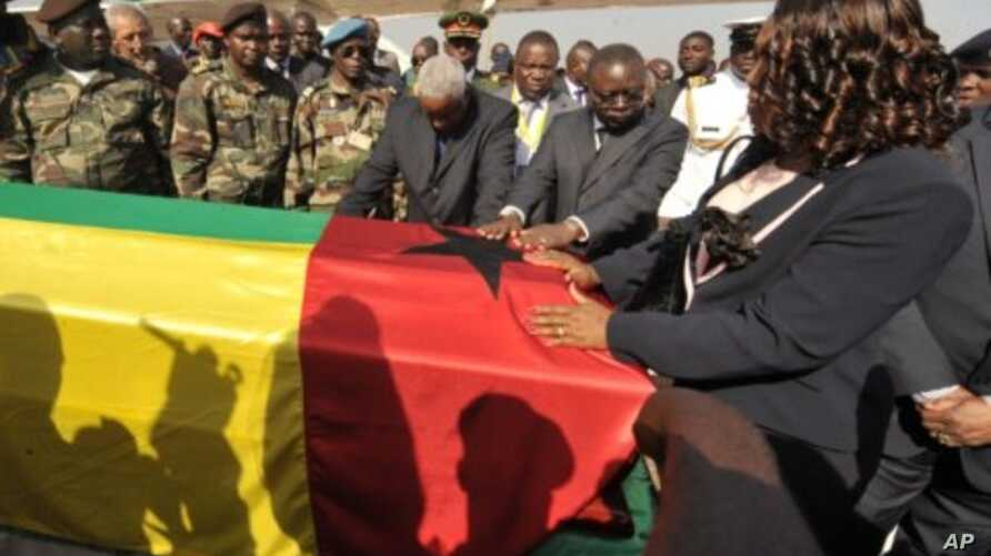 Guinea-Bissau's interim President Raimundo Pereira (C) touches on January 14, 2012 the coffin of late President Malam Bacai Sanha, who died in on January 9, 2012 at a Paris hospital, upon its return to Bissau.